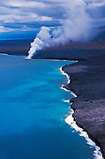 Old lava flows and coastline near Kalapana (steam from eruption site visible), Hawaii Volcanoes National Park, The Big Island, Hawaii USA