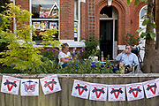 As the Coronavirus lockdown continues over the May Bank Holiday, the nation commemorates the 75th anniversary of VE Day (Victory in Europe Day, the day that Germany officially surrendered in 1945) and in Dulwich, neighbours and residents emerge from their homes to party while still observing social distancing rules. A couple drink Pims outside their home, on 8th May 2020, in London, England.