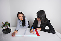 Happy businesswomen working at desk in office