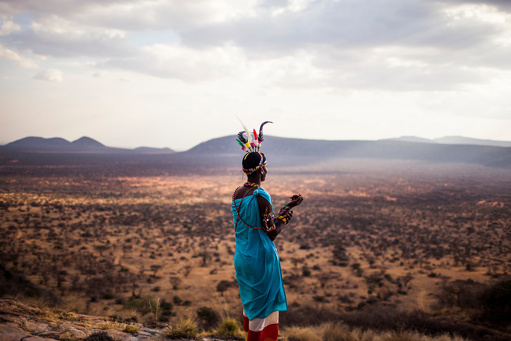 A Masai warrior overlooks an epic desert landscape in the early morning hours in Kenya.