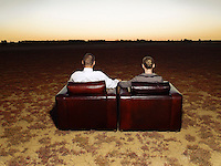 Couple watching sunset sitting in armchairs in open plain back view