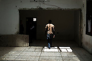 Libia, Tripoli: African migrant is seen inside his cell at Abu Salim detention center for illegal migrants. Alessio Romenzi