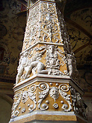 Interior detail from the Palazzo Vecchio, Florence, Italy. A massive, Romanesque fortress-palace designed by the architect Arnolfo di Cambio. Internally, The first courtyard was designed in 1453 by Michelozzo. In the lunettes, high around the courtyard, are crests of the Church and City Guilds. In the centre, the porphyry fountain is by Battista del Tadda. This image shows a column covered in decorative reliefs.