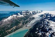 """Reid Glacier melts into Reid Inlet. Flightseeing from Skagway or Haines is a spectacular way to see Glacier Bay National Park, in Alaska, USA. We were bedazzled by Mountain Flying Service's 1.3-hour West Arm tour from Skagway. Glacier Bay is honored by UNESCO as part of a huge Biosphere Reserve and World Heritage site shared between Canada and the United States. In 1750-80, Glacier Bay was totally covered by ice, which has since radically melted away. In 1794, Captain George Vancover found Icy Strait on the Gulf of Alaska choked with ice, and all but a 3-mile indentation of Glacier Bay was filled by a huge tongue of the Grand Pacific Glacier, 4000 feet deep and 20 miles wide. By 1879, naturalist John Muir reported that the ice had retreated 48 miles up the bay. In 1890, """"Glacier Bay"""" was named by Captain Beardslee of the U.S. Navy. Over the last 200 years, melting glaciers have exposed 65 miles of ocean. As of 2019, glaciers cover only 27% of the Park area. Since the mid 1900s, Alaska has warmed 3 degrees Fahrenheit and its winters have warmed nearly 6 degrees. Human-caused climate change induced by emissions of greenhouse gases continues to accelerate warming at an unprecedented rate. Climate change is having disproportionate effects in the Arctic, which is heating up twice as fast as the rest of Earth."""