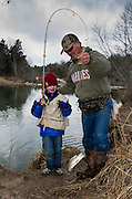 Mark Hanks from Edmond, Oklahoma helps his grandson Lane Hanks land a nice sized rainbow trout caught at the Blue River near Tishomingo, Oklahoma