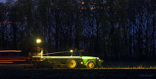 A John Deere tractor pulls a sugar beet harvester while a another tractor pulls a semi truck along side.