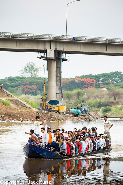 23 MAY 2013 - MAE SOT, TAK, THAILAND: A boat full of Burmese come down the Moei River to an unofficial border crossing point in Mae Sot, Thailand. Most are people coming to Mae Sot for shopping or health care. Fifty years of political turmoil in Burma (Myanmar) has led millions of Burmese to leave their country. Many have settled in neighboring Thailand. Mae Sot, on the Mae Nam Moei (Moei River) is the center of the Burmese emigre community in central western Thailand. There are hundreds of thousands of Burmese refugees and migrants in the area. Many live a shadowy existence without papers and without recourse if they cross Thai authorities. The Burmese have their own schools and hospitals (with funding provided by NGOs). Burmese restaurants and tea houses are common in the area.   PHOTO BY JACK KURTZ