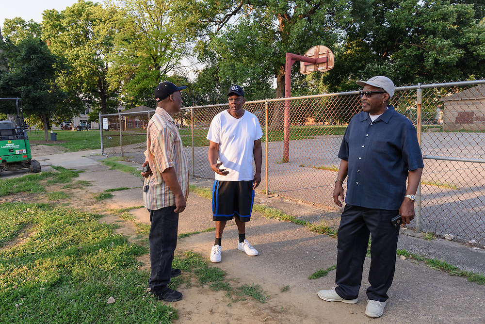 Norman Martin, Street Peace's team coordinator, left, speaks with Willee Hendricks on 12th Street Monday, June 20, 2016 along Baxter Park in the Beecher Terrace neighborhood as Eddie Woods watches the scene. (Photo by Brian Bohannon)
