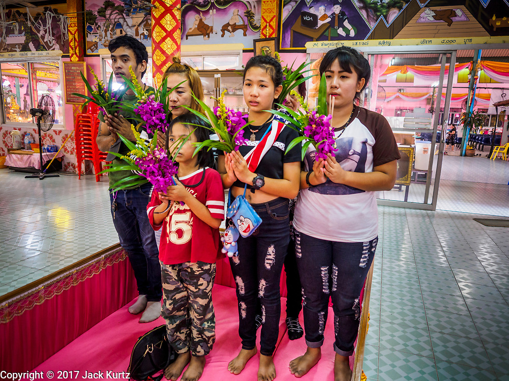 """29 MARCH 2017 - BANG KRUAI, NONTHABURI, THAILAND:  A family stands in the family sized coffin before their ritualistic death at Wat Ta Kien (also spelled Wat Tahkian), a Buddhist temple in the suburbs of Bangkok. People go to the temple to participate in a """"Resurrection Ceremony."""" Groups of people meet and pray with the temple's Buddhist monks. Then they lie in coffins, the monks pull a pink sheet over them, symbolizing their ritualistic death. The sheet is then pulled back, and people sit up in the coffin, symbolizing their ritualist rebirth. The ceremony is supposed to expunge bad karma and bad luck from a person's life and also get people used to the idea of the inevitability of death. Most times, one person lays in one coffin, but there is family sized coffin that can accommodate up to six people. The temple has been doing the resurrection ceremonies for about nine years.         PHOTO BY JACK KURTZ"""