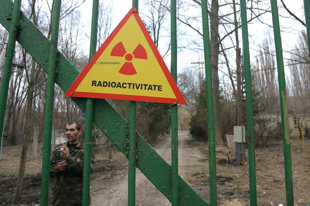 Ein Sicherheitsbeamter hinter dem Zaun einer Deponie für schwach- und mittelradioaktiven Abfall bei Chisinau, Moldau. / A radioactive symbol and a security officer behind the fence of a nuclear waste dump near Chisinau, Moldova.