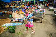 10 MARCH 2013 - VANG VIENG, LAOS: A girl and her brother walk through the market in Vang Vieng, Laos.     PHOTO BY JACK KURTZ