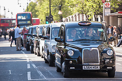 "© Licensed to London News Pictures. 21/04/2015. Oxford Street, London, UK. London black cab taxi drivers, members of the United Cabbies Group, take part in the ""Enough is Enough"" protest bringing the normally busy Oxford Street to a standstill.  They were demonstrating against Transport for London, their regulator, for refusing to enforce their own regulations leaving Londoners' safety at risk.   Photo credit : Stephen Chung/LNP"