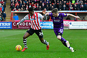 Chiedozie Ogbene (24) of Exeter City on the attack chased by Harry Clifton (15) of Grimsby Town during the EFL Sky Bet League 2 match between Exeter City and Grimsby Town FC at St James' Park, Exeter, England on 29 December 2018.