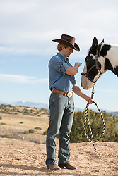 cowboy outdoors petting a horse