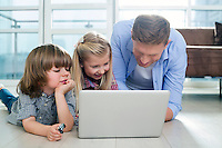Happy father with children using laptop on floor in living room