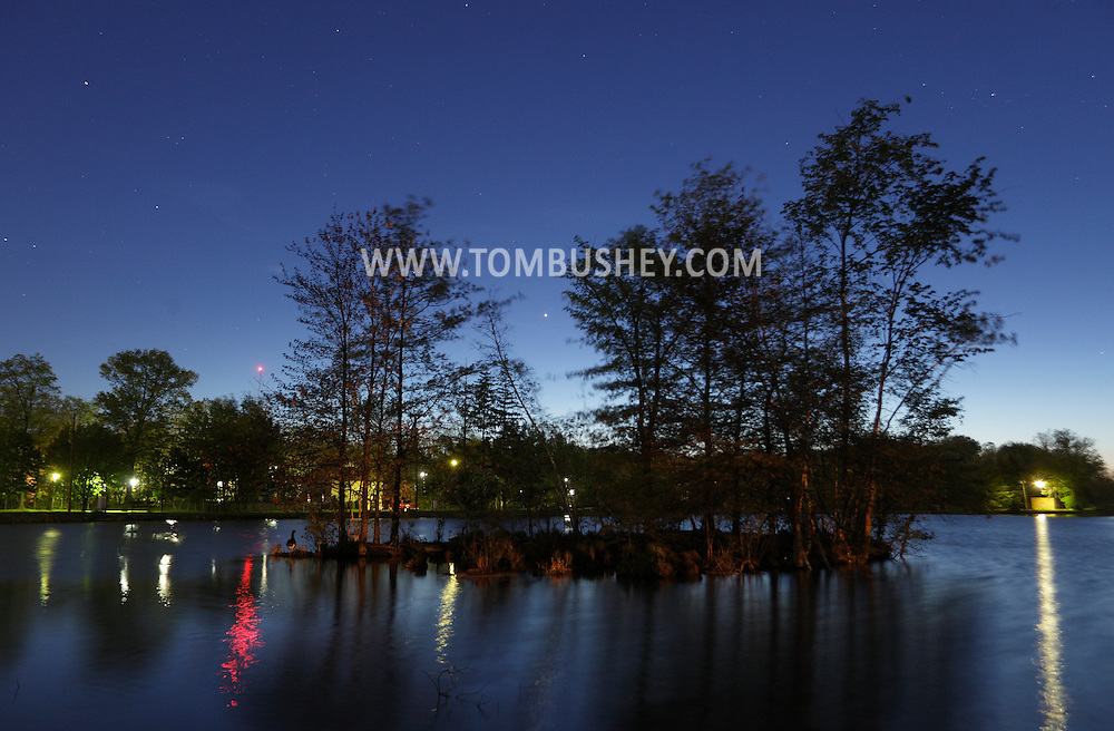 Middletown, New York - Lights are reflected in the lake at Fancher-Davidge Park in Middletown at twilight on April 27, 2010. Stars and the planet Venus (seen at center between the trees on the island) are also visible in the six-second exposure