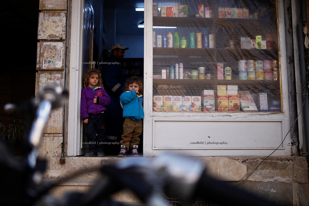 Children wait in the entrance of a drugstore in Deir az-Zor. Residents of eastern syrian town Deir az-Zor joined arab spring protests against the regime of Bashar al-Assad from its early beginning in March 2011. Since summer 2012 the town with few hundred thousand inhabitants is embattled between the Syrian Army and different opposing rebel groups like Free Syrian Army and Jabhat al-Nusra. Deir az-Zor is target to constant shelling by artillery, war planes and short range missiles. Almost 70 percent of the town is rebel held while government forces remain in control over some residental areas and a strategic important airport. Deir az-Zor is widely damaged and some areas almost totally destroyed by fierce and long lasting battles. All direct road connections to Deir az-Zor are cut and fighters and returning residents as well depend on one provisional supply line across the Euphrates river which is regularly targeted by government snipers.