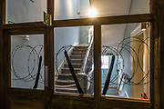 "Barbed wire on Exit stairwell. Scheduled to run through 2018 at York Castle Museum, the First World War Exhibition, ""1914: When the World Changed Forever"" opened on 28 June 2014, exactly 100 years after Archduke Franz Ferdinand was assassinated, sparking a chain of events leading to war. York Castle Museum was founded in 1938 by Dr John Kirk, a doctor from Pickering, North Yorkshire. The museum houses Kirk's extraordinary collection of social history, reflecting everyday life in the county, including a fullscale Victorian reconstruction of Kirkgate street, a recreated Jacobean dining rooms (1567–1625), a history of children's toys, and exhibits on the First World War through the 1960s. The York Castle Museum is housed in a former debtors' prison (built in 1701–05 using stone from castle ruins) and in an adjoining former women's prison (built 1780–85) in North Yorkshire, England. Originally built by William the Conqueror in 1068, York Castle features a ruined keep now called ""Clifford's Tower."""