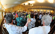 Women raise hands while praying the Our Father during Mass at Wisconsin Catholic church. (Sam Lucero photo)
