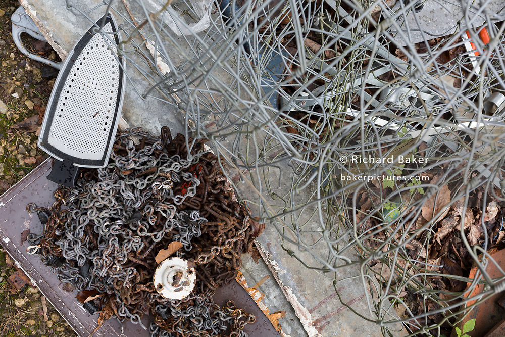 Household objects scrap metal including chain, an iron and fencing await recycling on rural land, on 30th July 2017, in Wrington, North Somerset, England.