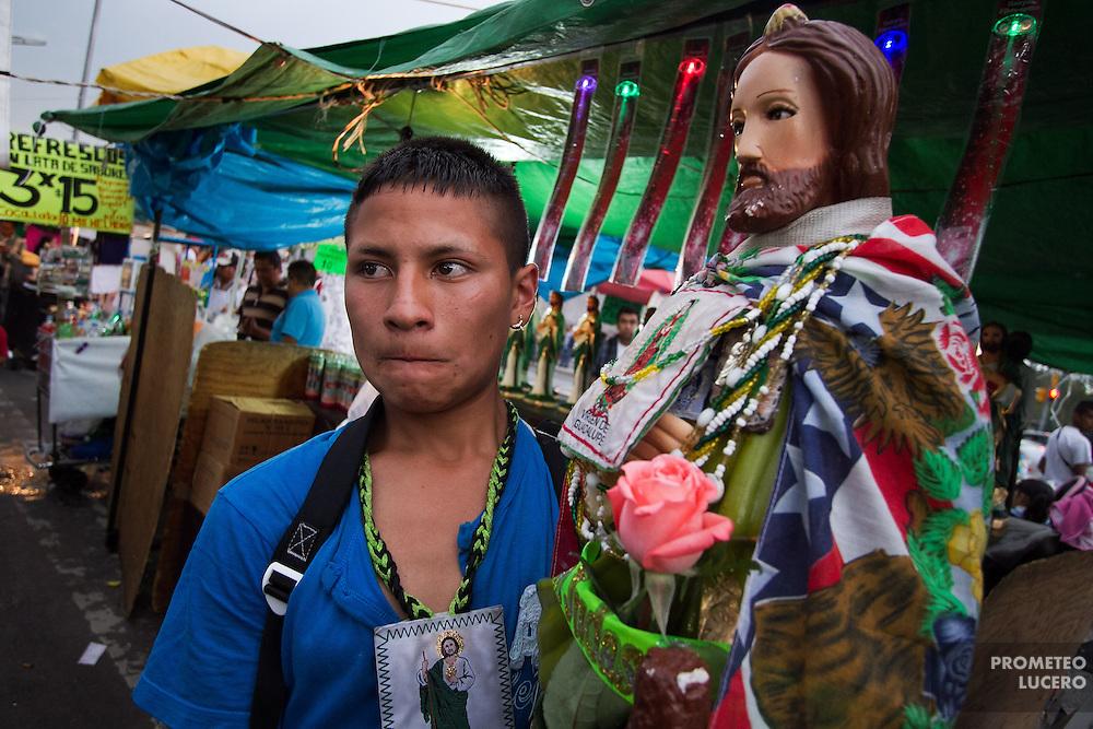Un joven carga una figura de San Judas Tadeo entre los puestos circundantes a la iglesia de San Hipólito en la Ciudad de México. La figura lleva una bandera de los Estados Unidos a la espalda. (Photo: Prometeo Lucero)