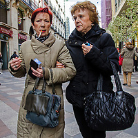 Dos mujeres caminando por las calles de Madrid. Two women walking and talking in the street of Madrid, Spain