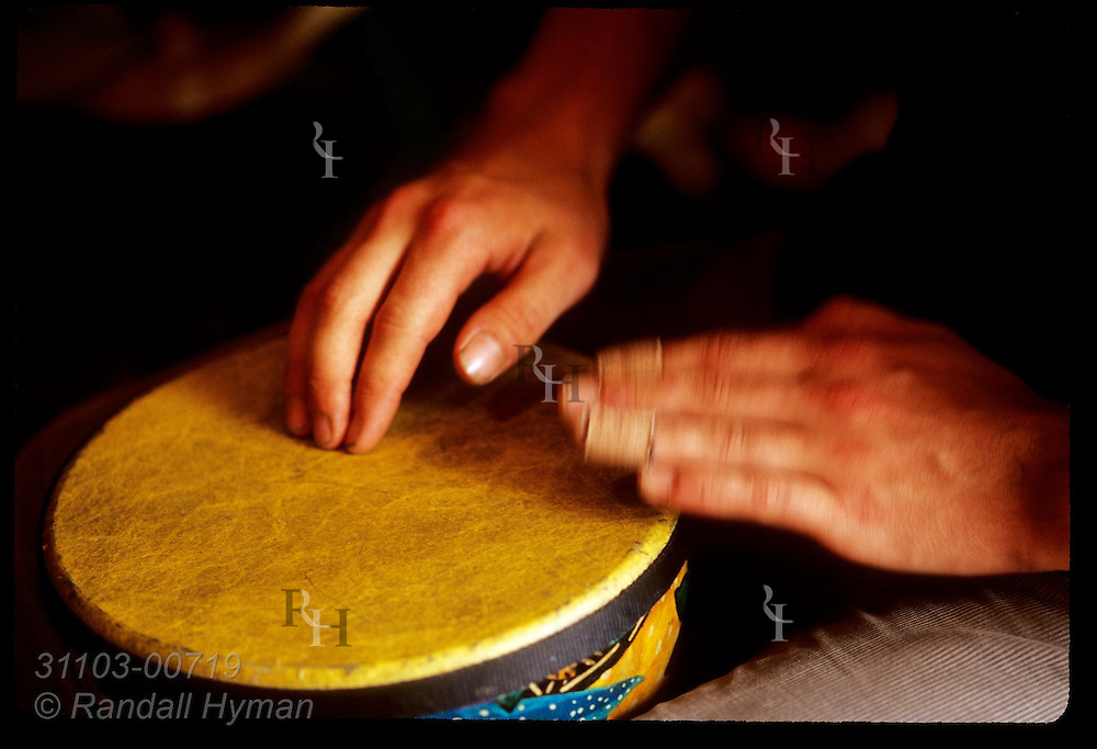 Bandaged fingers tap out rhythm on a small hand drum during a  performance in town of Dingle, Ireland.