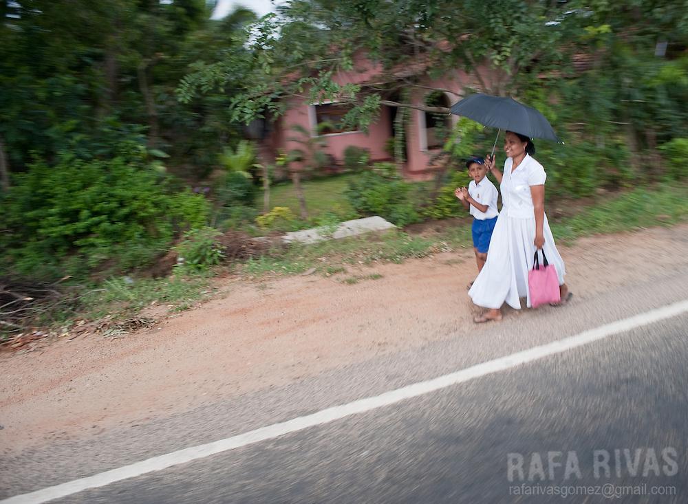 Locals walk alongside a road in Tissamaharama, Sri Lanka, on February 2011. Photo Rafa Rivas