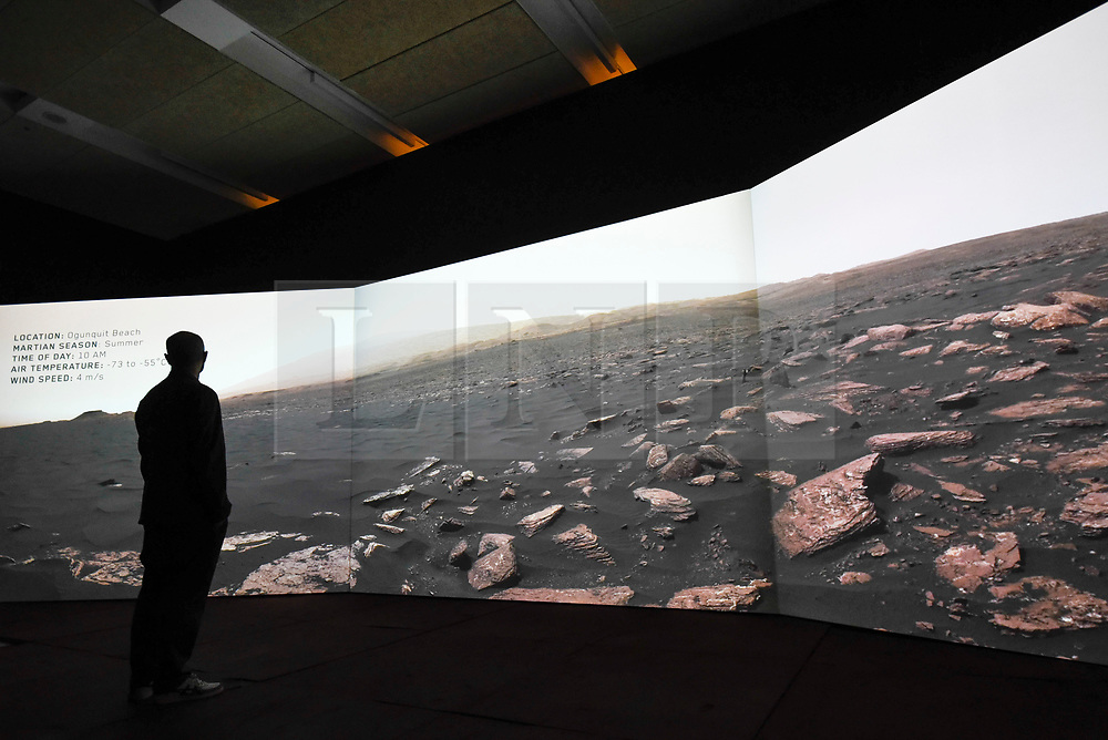 """© Licensed to London News Pictures. 17/10/2019. LONDON, UK. A staff member views a video projection showing the view on Mars from the Curiosity rover. Preview of """"Moving to Mars"""" at the Design Museum. The exhibition explores how sending humans to Mars is a frontier for science as well as design and features over 200 exhibits from NASA, the European Space Agency together with new commissions.  The show is open 18 October to 23 February 2020.  Photo credit: Stephen Chung/LNP"""