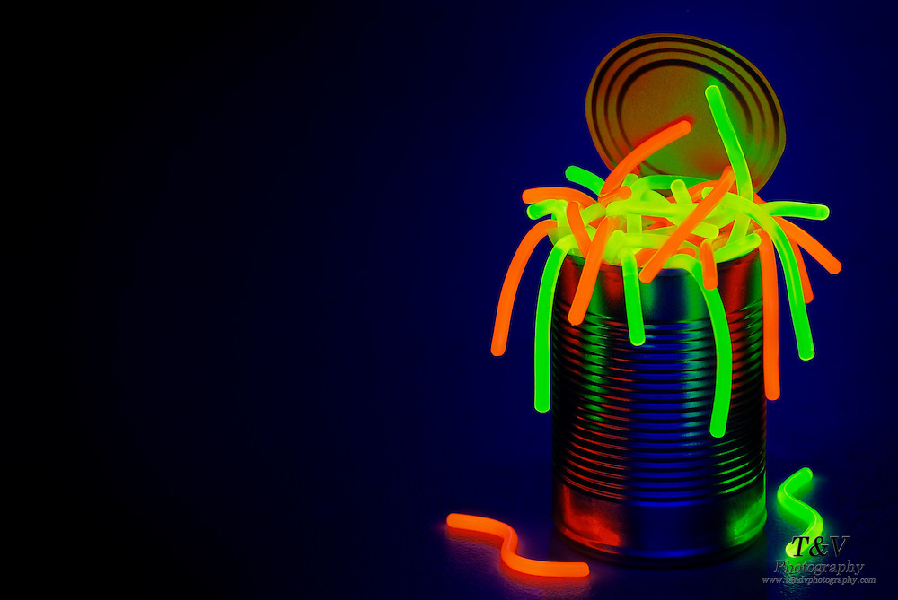 A open can full of glowing worms against a dark blue background.Black light