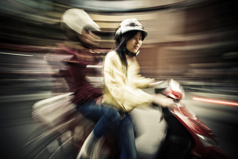 A young girl snaps into focus as she drives her friend on the back of a scooter in Hanoi's French Quarter, Vietnam