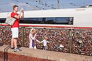 Europa, Deutschland, Koeln, Vorhaengeschloesser als Liebesschloesser (ital. Lucchetti d'Amore) am Zaun entlang des Fussweges der Hohenzollernbruecke ueber den Rhein. Die Schloesser mit Gravuren werden nach einem Brauch von Verliebten an Bruecken angebracht. Der Schluessel wird anschliessend in den Rhein geworfen, junge Frau macht Fotos.<br /> <br /> Europe, Germany, Cologne, padlocks on fence of footpath of the Hohenzollern railway bridge. Young couples seal their love with engraved padlocks and throw the key into the flowing river Rhine below, young woman takes pictures.
