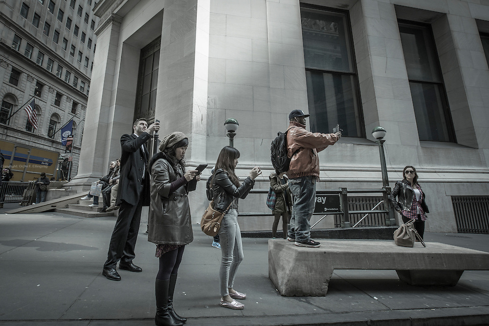 Tourists snap their photos and selfies outside the famous facade of the NYSE - New York Stock Exchange.