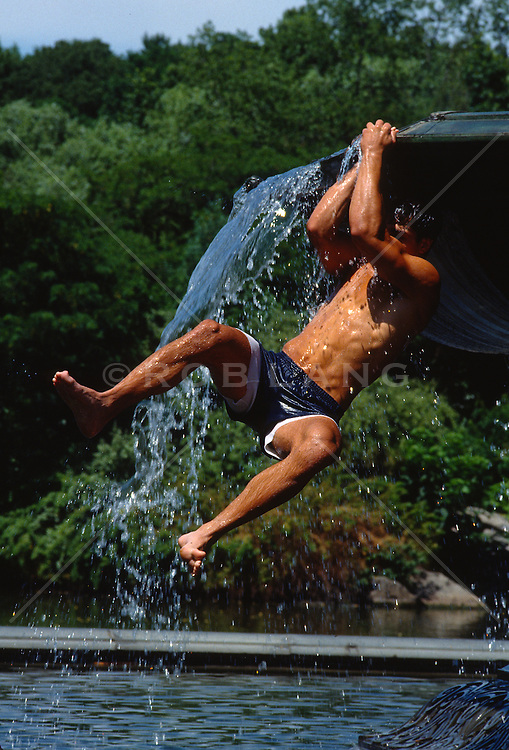 sexy man hanging off of a fountain in New York City