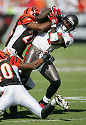 TAMPA, FL - OCTOBER 15:  Wide receiver Joey Galloway #84 of the Tampa Bay Buccaneers holds onto a pass reception while getting tackled by cornerback Tory James #20 and safety Madieu Williams #40 of the Cincinnati Bengals at Raymond James Stadium on October 15, 2006 in Tampa, Florida. The Bucs defeated the Bengals 14-13. (©Paul Anthony Spinelli) *** Local Caption *** Joey Galloway;Tory James;Madieu Williams