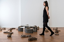 "© Licensed to London News Pictures. 17/04/2018. LONDON, UK. A staff member walks amongst 38 clay sculptures called ""Urtiere (Primordial Animals)"", 1958/1982, with (C) ""Hirsch (Stag)"", 1958/1982, a teak wood and wooden ironing board that belonged to the artist's mother , at the preview of ""Joseph Beuys: Utopia at the Stag Monuments"", at the Galerie Thaddaeus Ropac in Dover Street.  The retrospective is the most important UK exhibition of Beuys' work in over a decade, presenting major sculptures and rarely seen works from 1947 to 1985, and runs from 18 April to 16 June.  Photo credit: Stephen Chung/LNP"