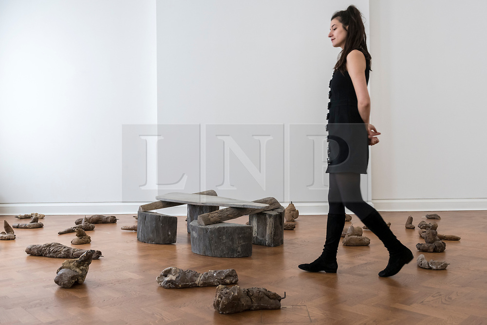 """© Licensed to London News Pictures. 17/04/2018. LONDON, UK. A staff member walks amongst 38 clay sculptures called """"Urtiere (Primordial Animals)"""", 1958/1982, with (C) """"Hirsch (Stag)"""", 1958/1982, a teak wood and wooden ironing board that belonged to the artist's mother , at the preview of """"Joseph Beuys: Utopia at the Stag Monuments"""", at the Galerie Thaddaeus Ropac in Dover Street.  The retrospective is the most important UK exhibition of Beuys' work in over a decade, presenting major sculptures and rarely seen works from 1947 to 1985, and runs from 18 April to 16 June.  Photo credit: Stephen Chung/LNP"""