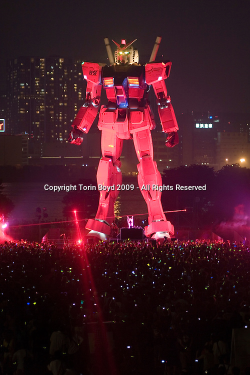 """This was a concert held on August 22, 2009 in Tokyo in which Japanese synthesizer artist Daisuke Asakura performed under the giant life size Gundam robot located in Shiokaze Park in Tokyo's Odaiba waterfront district. Officially called """"Daisuke Asakura Club Event Seq Virus 2009 G-Remix Night"""", it was attended by thousands of fans of both Asakura and the Gundam robot franchise. This 59-foot-tall (18-meters) Gundam robot was constructed to celebrate the 30th anniversary of the original Gundam character created by Yoshiyuki Tomino and Sunrise studios in 1979. This was a TV series called Mobile Suit Gundam, but since then the Gundam character has grown into a more than $500 million (50 Billion JPY) trademark owned by NAMCO BANDAI Holdings Inc. of Japan. The giant robot which emits lights, steam, and rotates it head was opened to the public in early July 2009 and will be dismantled in September. It is officially called the """"Green Tokyo Gundam Project""""."""