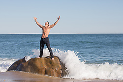 shirtless man on a rock in the ocean with arms up to the sky