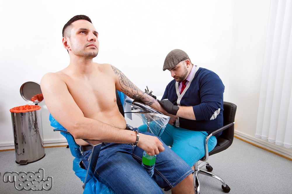 Shirtless young man getting tattooed from artist in tattoo shop