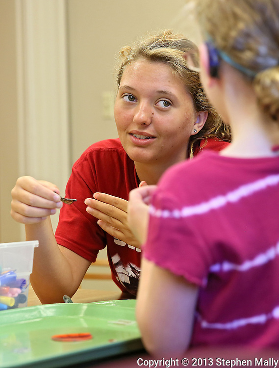 Student Volunteer Jaymee Keen, 14, of Ames signs as she talks with a camper during a summer camp hosted by the Iowa School for the Deaf at the Iowa Braille and Sight Saving School in Vinton on Tuesday, July 16, 2013. Keen is a student at the Iowa School for the Deaf.