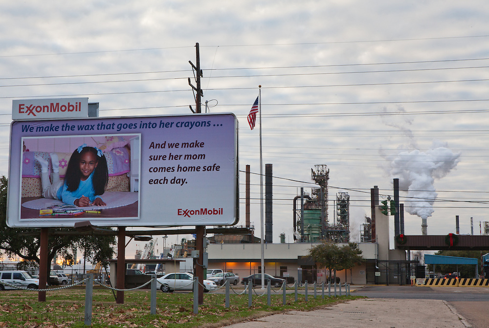 """Public relations sign at Exxon Mobile refinery in Baton Rouge, Louisiana on Scenic Highway located in the stretch between Baton Rouge and New Orleans along the river, is part of a large concentration of chemical and oil companies that was formerly referred to as the """"Petrochemical Corridor,"""" but now is know as """"Cancer Alley.""""  Many cases of cancer have occurred  in communities on both sides of the river though the Louisiana Tumor Registry claims the numbers are not higher then the national average. The record high levels of the Mississippi River in the spring of 2011 brought on by what some scientists classify as climate change,  threaten the environment with the potential flooding of industrial complexes and nuclear facilities along the river."""