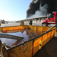 Lines pump water from a holding pond for fire fighters to use to fight the fire at American Furniture Friday morning. The departments had to use several of the ponds and shuttle in water since their was no frire hyrdrants near the plant for them to use.