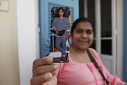 A Sri Lankan woman shows a picture of herself taken when she first came to Beirut 30 years ago.