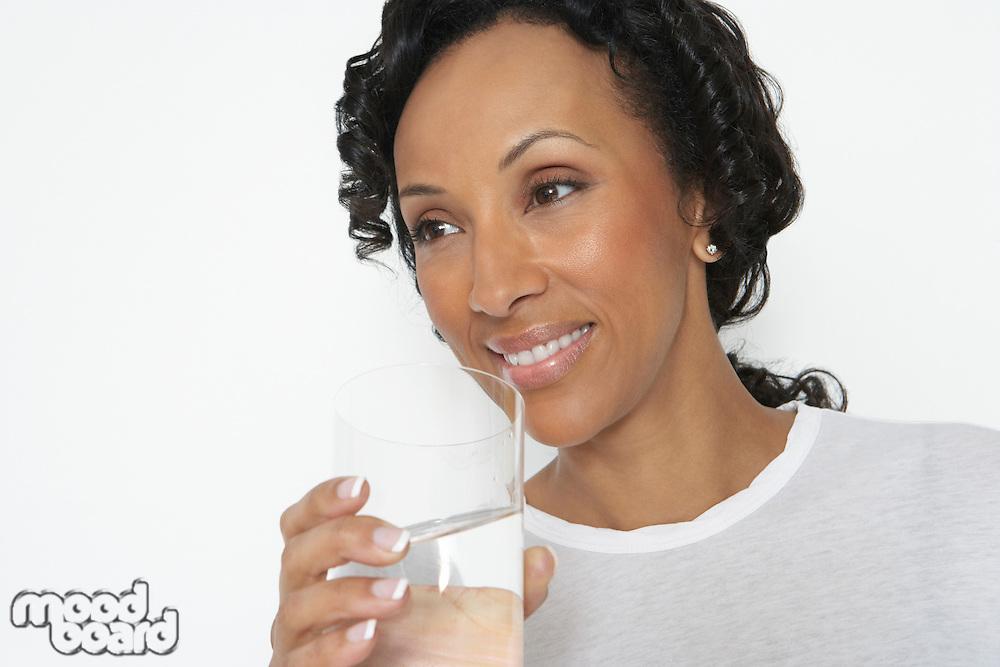 Woman drinking glass of water, studio shot