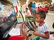 11 JULY 2011 - BANGKOK, THAILAND:  A boy plays a video game while he waits to board to a train in Hua Lamphong in Bangkok. Hua Lamphong Grand Central Railway Station, officially known as the Bangkok Grand Central Terminal Railway Station, is the main railway station in Bangkok, Thailand. It is located in the center of the city in Pathum Wan District, and is operated by the State Railway of Thailand. The station was opened on 25 June 1916, after six years' construction. The station was built in an Italian Neo-Renaissance style, with decorated wooden roofs and stained glass windows. The architecture is attributed to Turin-born Mario Tamagno, who, with countryman Annibale Rigotti made a mark on early 20th century public building in Bangkok. The pair also designed Bang Khun Prom Palace (1906), Ananda Samakhom Throne Hall in The Royal Plaza (1907-15) and Suan Kularb Residential Hall and Throne Hall in Dusit Garden, among other buildings..There are 14 platforms and 26 ticket booths. Hua Lamphong serves over 130 trains and approximately 60,000 passengers each day. Thailand has the most advanced rail system in Southeast Asia and trains from Hua Lamphong serve all corners of the Kingdom.       PHOTO BY JACK KURTZ