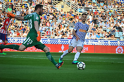 April 19, 2018 - San Sebastian, Spain - Oblak of Atletico Madrid duels for the ball with Sergio Canales of Real Sociedad during the Spanish league football match between Real Sociedad and Atletico Madrid at the Anoeta Stadium on 19 April 2018 in San Sebastian, Spain  (Credit Image: © Jose Ignacio Unanue/NurPhoto via ZUMA Press)