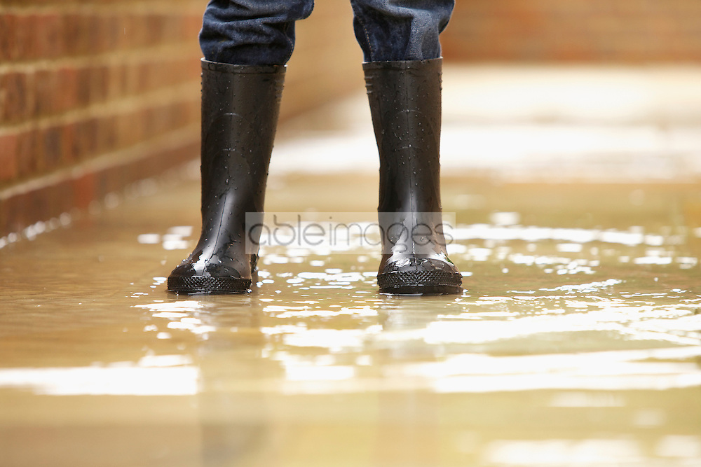Boy's Legs in Wellington Boots on Flooded Pavement