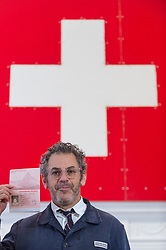 "© Licensed to London News Pictures. 05/10/2018. LONDON, UK. Tom Sachs poses with a passport next to the Swiss flag. Preview of ""Swiss Passport Office"" by American artist Tom Sachs at Galerie Thaddaeus Ropac in Mayfair.  To coincide with Frieze Week, the gallery will remain open for 24 hours from 6pm 5 October to 6pm 7 October for the issuing of serial-numbered Tom Sachs Swiss passports for visitors.  The installation reflects the concerns relating to Brexit, Syria and Donald Trump's immigration policies and challenges the notion of global citizenship.  Photo credit: Stephen Chung/LNP"