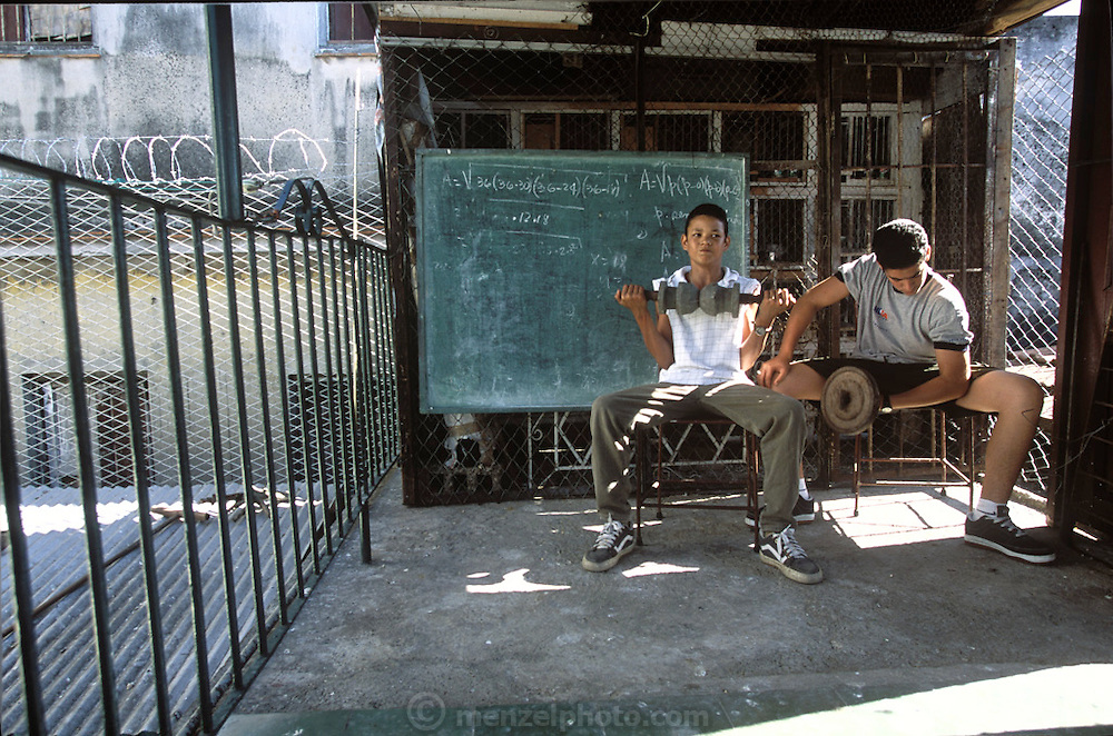 (MODEL RELEASED IMAGE). The Costa grandsons, Javier (right) and Ariel, exercise daily on the roof of the family home in Havana, Cuba. Behind them are a blackboard with math homework and cages for the family's pigeons. (Supporting image from the project Hungry Planet: What the World Eats.)